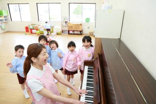 ピアノを弾く先生と歌う子供たち