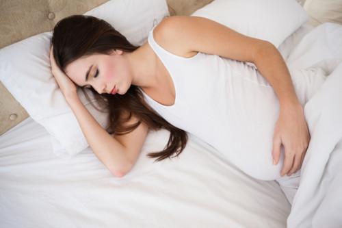 腹痛で寝ている妊婦