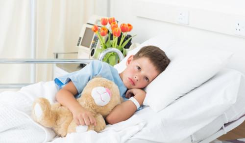 病院のベッドで横になる子供